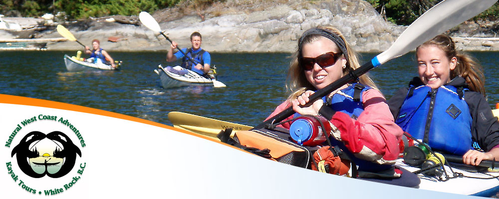 Photo of two ladies sharing a two-seater kayak and smiling
